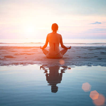 minds: Woman practicing yoga on the beach at sunset, with reflection in water  Stock Photo