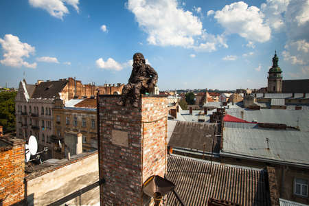 judged: LVIV, UKRAINE - AUG 6: Chimneysweep monument is on the roof of a historic building House of Legends on Aug 6, 2012 in Lviv, Ukraine. On 12 Jun 2009 the Ukrainian magazine Focus judged Lviv the best Ukrainian city to live in.