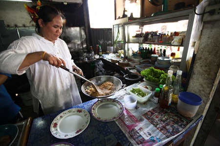 CHANG, THAILAND - JANUARY 23: Unknown vendors prepare food at a street side restaurant on Jan 23, 2012 in Chang, Thai. Government figures indicate more 16,000 registered street vendors in Thailand.