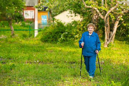 action fund: Active old woman nordic walking outdoors  85 years