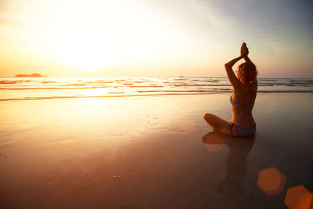 Yoga woman sitting on sea coast at sunset. photo
