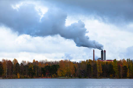 emissions: Air pollution by smoke coming out of three factory chimneys