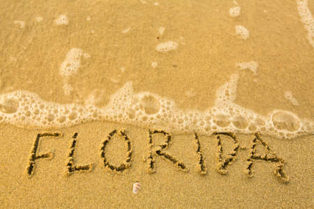 Florida - written in sand on beach texture - soft wave of the sea  photo