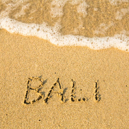 Bali - written in sand on beach texture - soft wave of the sea  Stock Photo