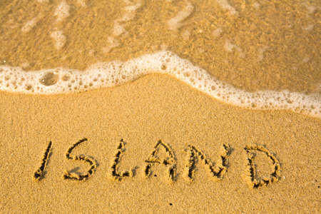 evoking: Island - written in sand on beach texture - soft wave of the sea