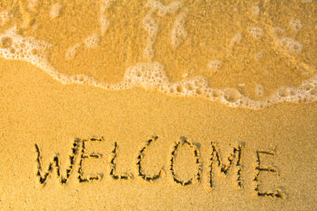 good heavens: Welcome - written in sand on beach texture - soft wave of the sea