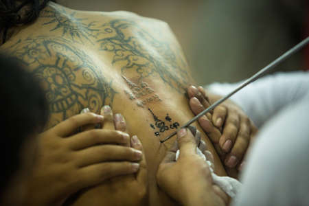 pra: NAKHON CHAI, THAILAND - MAR 23: Unidentified monk makes traditional Yantra tattooing during Wai Kroo Master Day Ceremony in Wat Bang Pra on Mar 23, 2013 in Nakhon Chai, Thailand. Editorial