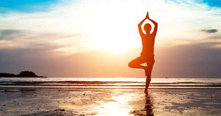 Silhouet jonge vrouw het beoefenen van yoga op het strand bij zonsondergang