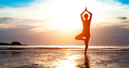 and harmony: Silhouette young woman practicing yoga on the beach at sunset Stock Photo