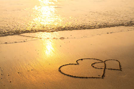 evoking: Hearts drawn on the sand of a beach, soft wave of the sea.