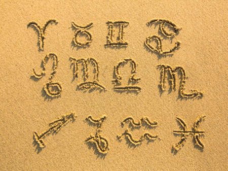 Set of zodiac signs drawn on the facture beach sand.  photo