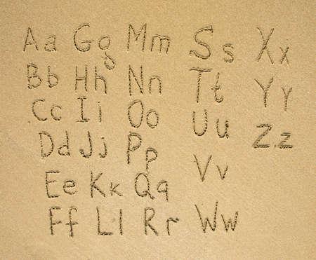 sand drawing: The alphabet written on a sand beach.