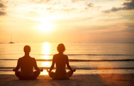 A young couple sitting on the beach of the sea in the lotus position at sunset, yoga practice photo