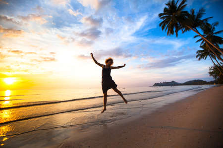 Young girl in a jump on the sea beach at sunset. photo