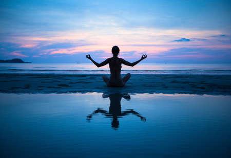 夕焼け (水の反射)、ビーチでのヨガの練習の女性