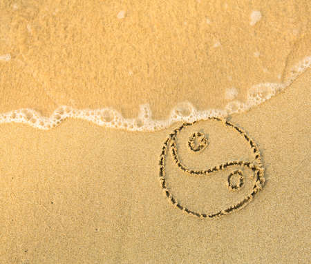 Yin yang symbol - written in sand on beach texture - soft wave of the sea  photo