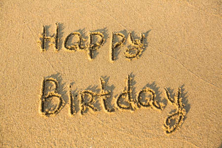 evoking: Happy Birthday -  the inscription, texture of sand.  Stock Photo