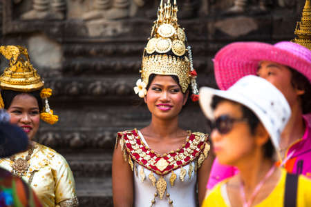 SIEM REAP, CAMBODIA - DEC 13: An unidentified cambodians in national dress poses for tourists in Angkor Wat, Dec 13, 2012 on Siem Reap, Cambodia. Angkor is the country's prime attraction for visitors. Stock Photo - 19298775