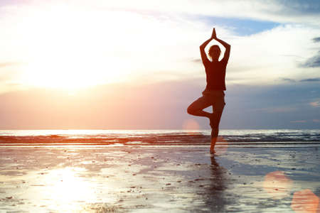 Silhouette woman practicing yoga on the beach at sunset Stock Photo - 19358726