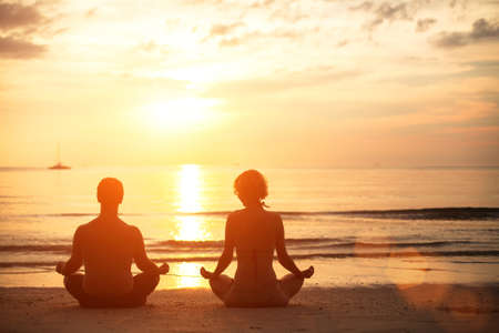 Young couple sitting on the beach of the sea in the lotus position at sunset, yoga practice photo