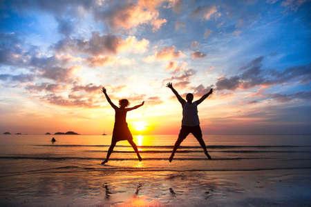 happy holidays: Jong koppel in een sprong op het strand zee bij zonsondergang concept van de langverwachte vakantie Stockfoto