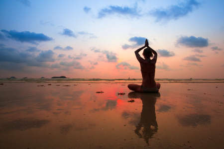Silhouette young woman practicing yoga on the beach at sunset photo