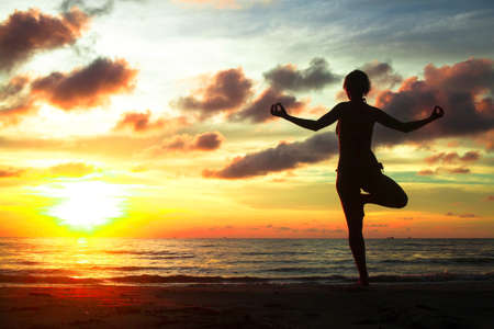 Young woman practicing yoga on the beach during sunset  photo