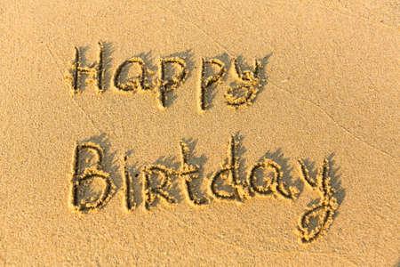 evoking: Inscription Happy Birthday on texture of sand