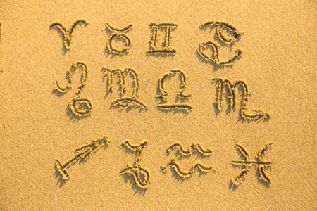 Set of zodiac signs - drawn on the facture beach sand   photo