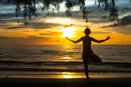Woman practicing yoga on the beach during sunset  photo