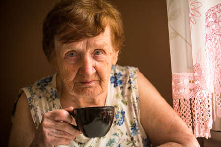Old woman is drinking tea Stock Photo