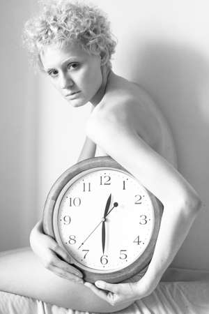 scrawny: Scrawny girl with big clock in hands, black and white photo.