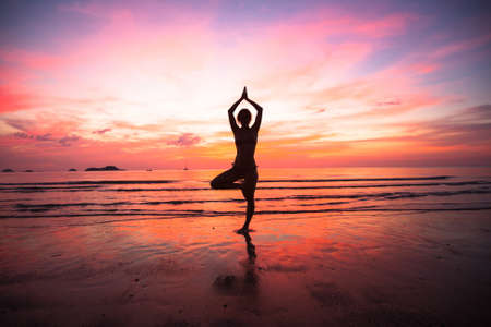 Young woman yoga practice at the seaside at sunset.