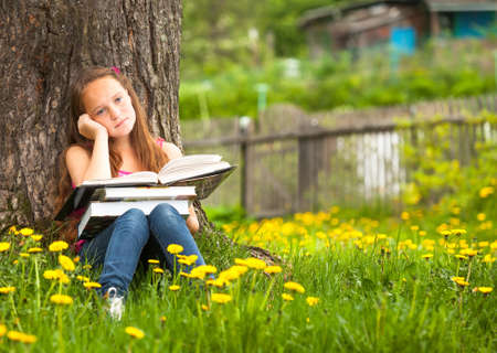 achiever: Tired teengirl with books in the village Stock Photo