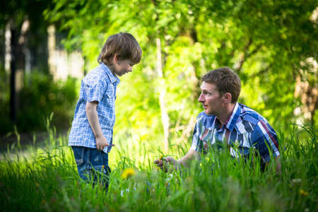 two generation family: Portrait of father and son play outdoors in the park Stock Photo