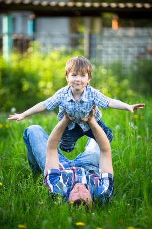 Baba ve oğul çimenlerin üzerinde parkta oynarken