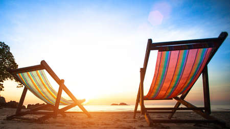 strandstoel: Ligstoelen op het verlaten kust zee bij zonsopgang Stockfoto