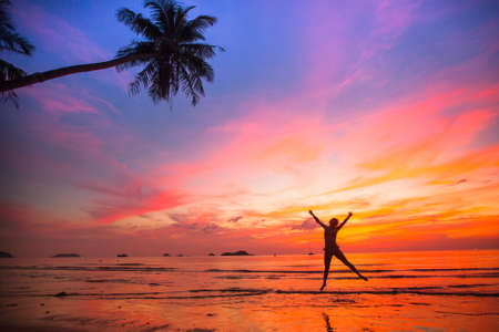 Young girl in a jump on the sea beach at sunset (concept of long-awaited vacation) Stock Photo