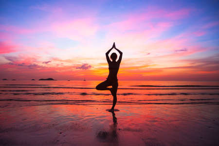 Silhouette woman yoga practice at the seaside at sunset. Stock Photo - 20573096