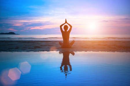 Gün batımında sahilde yoga siluet genç kadın
