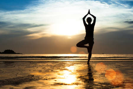Silhouette of a young woman practicing yoga on the beach at sunset