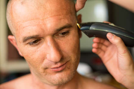 Close-up: Adult man being shaved at the hair salon. photo