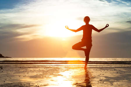 Silhouette woman practicing yoga on the beach at sunset. Stock Photo - 21141840
