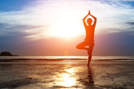 Silhouette woman practicing yoga on the beach at sunset. Stock Photo