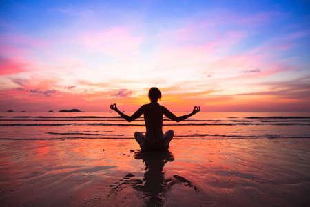 Sunset yoga woman on sea coast. photo