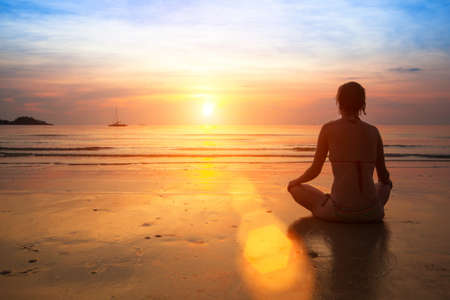 Woman practicing yoga on the ocean beach at sunset. Stock Photo - 21145318