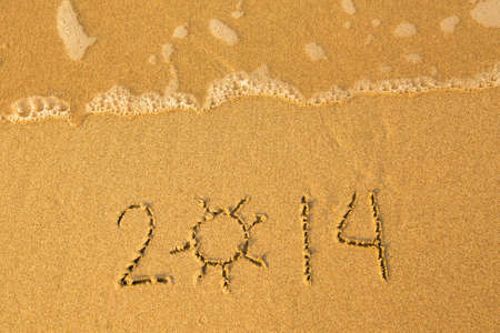 2014 - written in sand on beach texture - soft wave of the sea. photo