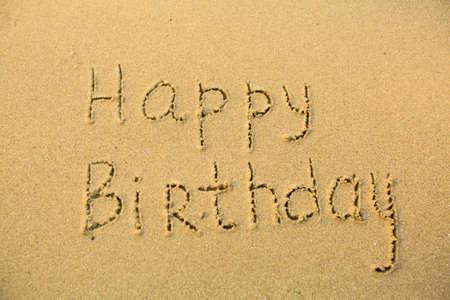 evoking: Inscription Happy Birthday on texture of wet sand.