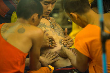 nakhon pathom: NAKHON CHAI, THAILAND - MAR 23: Unidentified monk makes traditional Yantra tattooing during Wai Kroo Master Day Ceremony in Wat Bang Pra on Mar 23, 2013 in Nakhon Chai, Thailand. Editorial