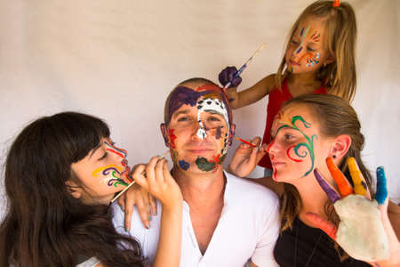 Happy family - children paints face of his father photo